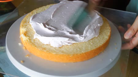 cakes : Baker decorating cake layer with whipped cream