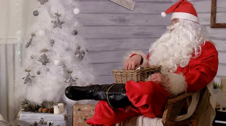 ameaça : santa is sitting in a chair and throwing toys Stock Footage