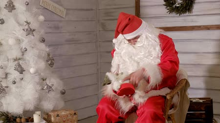 ameaças : santa is sitting in a chair and trying to stuff a toy as a gift