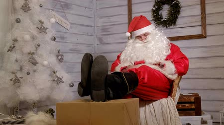 ameaça : santa is sitting in a chair putting his feet on a gift