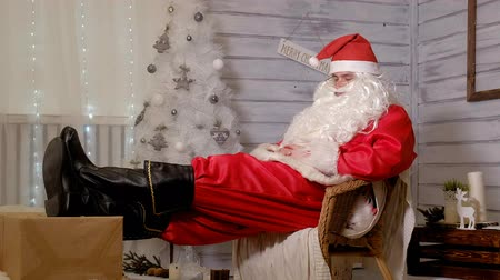 ameaças : santa is sitting in a chair putting his feet on a gift