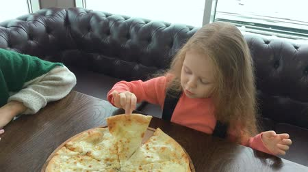 жевать : Little child girl portrait eat chew a piece of pizza Margarita in a pizzeria restaurant