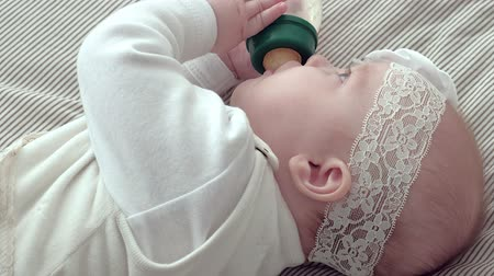 infant formula : Smiling baby girl lying down while drinking milk from a bottle