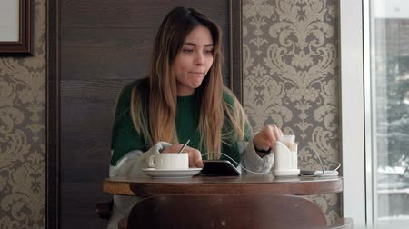 sending : Woman texting, sending sms on smartphone in cafe