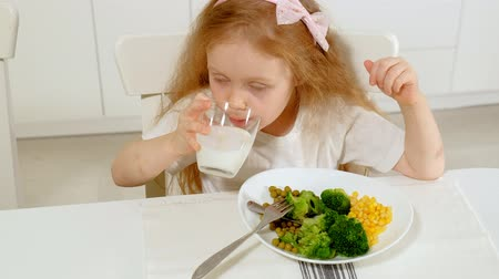 bezelye : A small beautiful girl eats broccoli and green peas with pleasure, at the table at home Stok Video