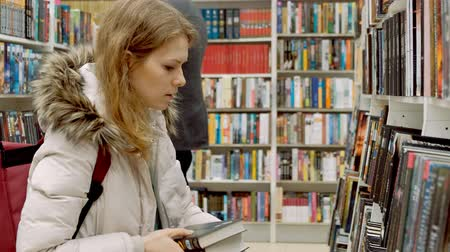 bookshop : Woman reading a book which she has just removed for a display on a shelf in a bookstore