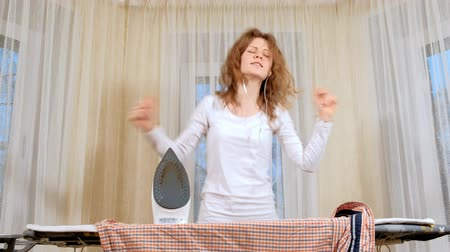 sprzataczka : Funny and beautiful woman ironing clothes and dancing at home