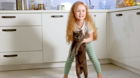 fur headphones : young beautiful girl is dancing in kitchen with her adorable cat