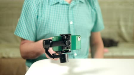 stabilizátor : The man adjusts the triaxial stabilizer for the phone