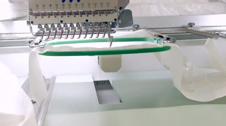 máquina : Textile - Professional and industrial embroidery machine. Machine embroidery is an embroidery process whereby a sewing machine or embroidery machine is used to create patterns on textiles. Stock Footage