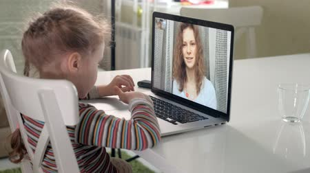 apple computers : little girl talking to mom via video callusing laptop