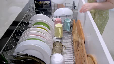 unload : The girl helps my mother put dishes out of the dishwasher