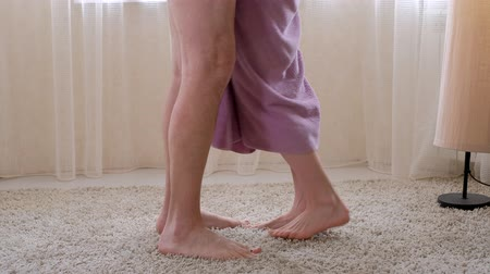 athletes foot : the man comes to the woman after the shower, the towel falls to the floor, feet closeup