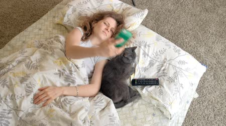 dragging : Sleeping with a cat, a woman waking up from a call pulling for the phone Stock Footage