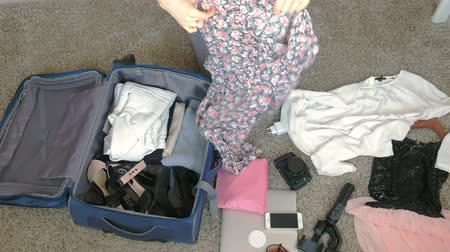 urlop : woman collects a suitcase in a home room.