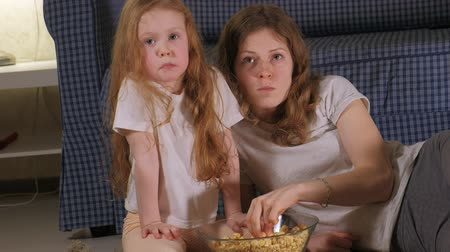 pukkanás : Happy loving family. Mother and her daughter child girl are eating popcorn On the floor in the room. front of the TV