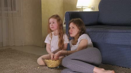 jídelna : Happy loving family. Mother and her daughter child girl are eating popcorn On the floor in the room. front of the TV