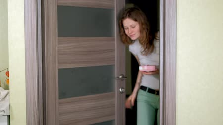oneperson : A woman enters the door and presents a gift in a box Stock Footage