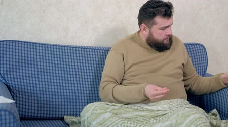 болеутоляющее : Man is drinking water with pills, sitting in bed.