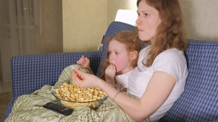 jídelna : Happy loving family. Mother and her daughter child girl are eating popcorn on the bed in the room. front of the TV