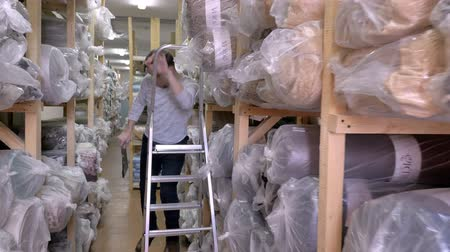 электронная коммерция : Auditor Counts Merchandise in Warehouse. He Walks Through Rows of Storage Racks with Merchandise. Slow motion Стоковые видеозаписи