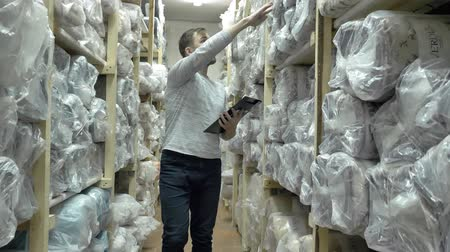 auditor : Auditor Counts Merchandise in Warehouse. He Walks Through Rows of Storage Racks with Merchandise. Slow motion Stock Footage