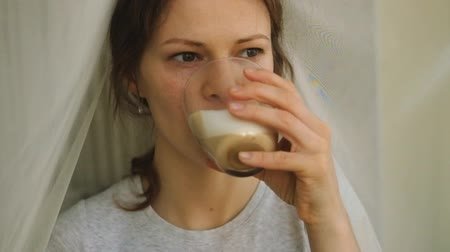 латте : young girl with freckles drinking cappuccino and eating a cake Стоковые видеозаписи