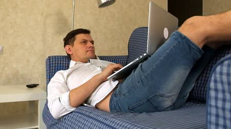freelance work : Young man working remotely lying on sofa with laptop.