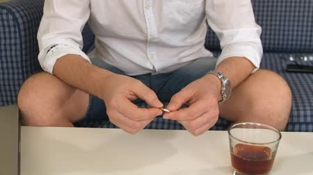 işlenmiş : man in right hand flask with alcohol, in left engagement ring. thinks, divorce. close-up