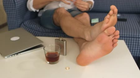 divorcement : a woman and a man take off the wedding rings and put them on the table. the husband takes a flask with an alcogol, on the table the legs of a man. close-up Stock Footage