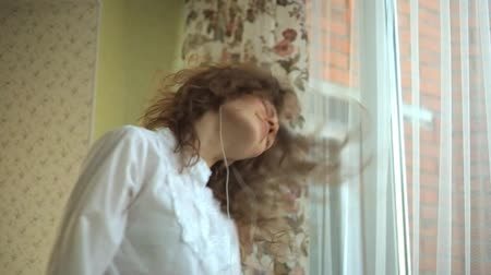 hravý : girl curly hair, actively twists her head, playful, listens to music in the headphones by the window, the phone in her hands, dances, singing. portrait Dostupné videozáznamy