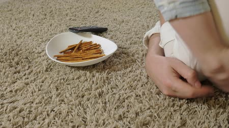 family watching tv : man and daughter watching television, sitting on the floor eating snacks Stock Footage