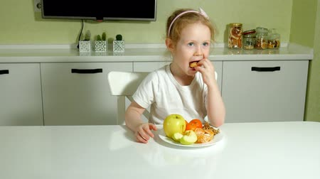решить : Beautiful cute little girl eating fruit, happy