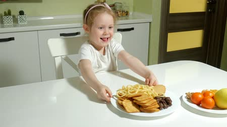 решить : Beautiful cute little girl refuses fruit, chooses cookies, chocolate, chips
