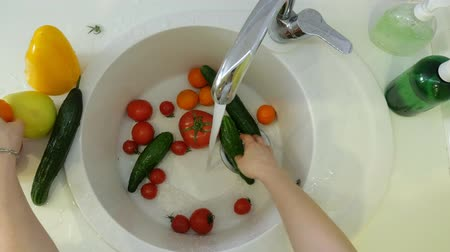 rajčata : Woman washes fresh vegetables under the tap in the sink in the kitchen