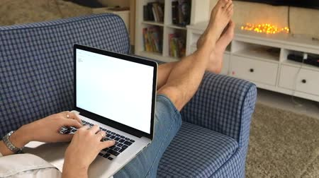kommunikátor : man lying on sofa in room working behind laptop Stock mozgókép