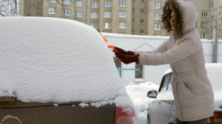 scraper : young woman clean car after snow storm with scraper Stock Footage