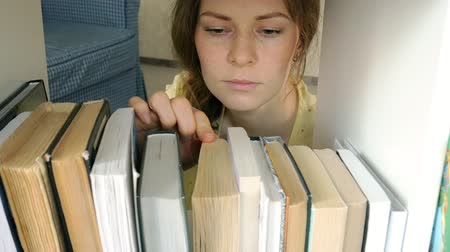 selecionando : young woman searching for a book. student selecting bookshelf library. female taking book from shelf in library. Vídeos