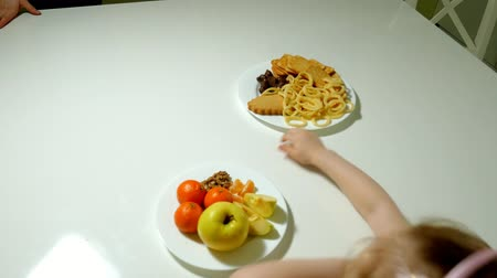 decidir : Beautiful cute girl refuses snacks, chocolate, chips, picks fruit. plates close-up Stock Footage