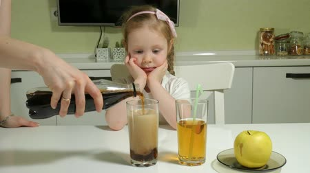 cola : a cute little girl is sitting at a table, chooses what to drink, cola or juice, the concept of a healthy lifestyle Stock Footage