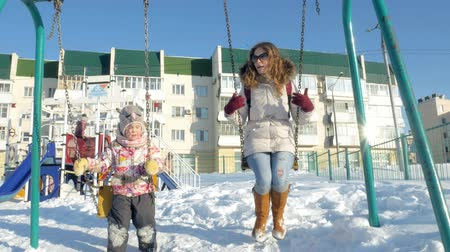 сказка : Young mother with child swinging on swing set outdoor in winter park. Snow falling, snowfall , winter time Стоковые видеозаписи