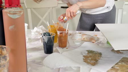 холст : woman prepares and paints paints for drawing a picture of fluid art