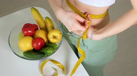measure tape : Slim woman measure waist on the background of a plate with fruits and vegetables, a healthy lifestyle