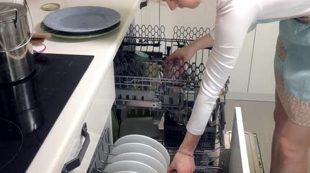 built up : A young woman lays a clean dish from a dishwasher