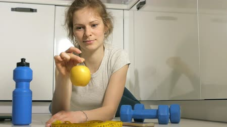 sports nutrition : Active athletic sportive woman with towel in sport outfit eating apple after the training Stock Footage