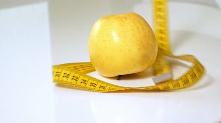 measure tape : Green apples measured the meter on a white