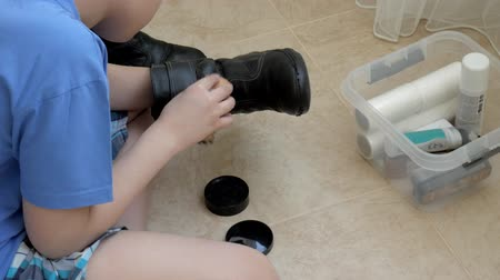 getting ready : The boy cleans his shoes with black cream and a brush Stock Footage