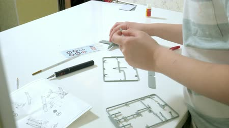 дисплей : The boy creates a plastic model airplane, an exact copy, from the designer Стоковые видеозаписи