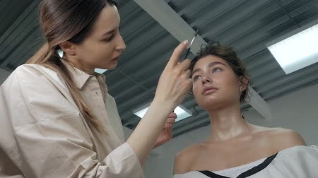 rímel : Young beautiful woman applying make-up by make-up artist