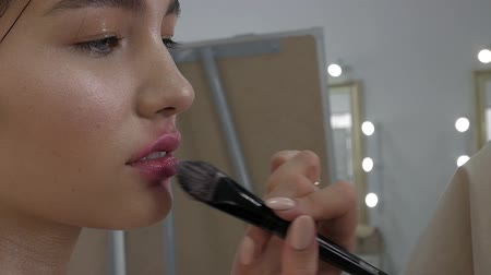 corar : Young beautiful woman applying make-up by make-up artist